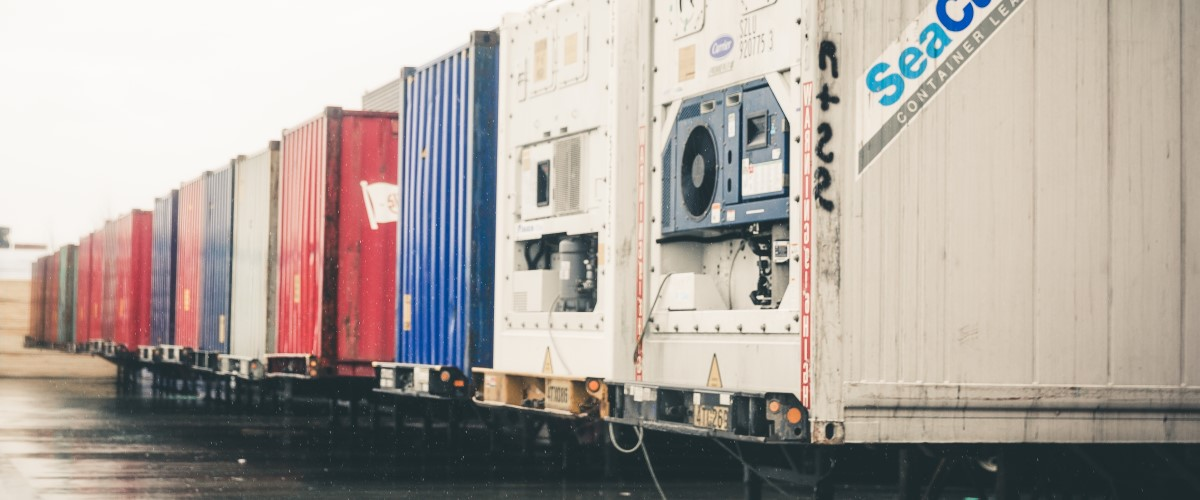 A row of ocean containers, with a reefer container being the closest