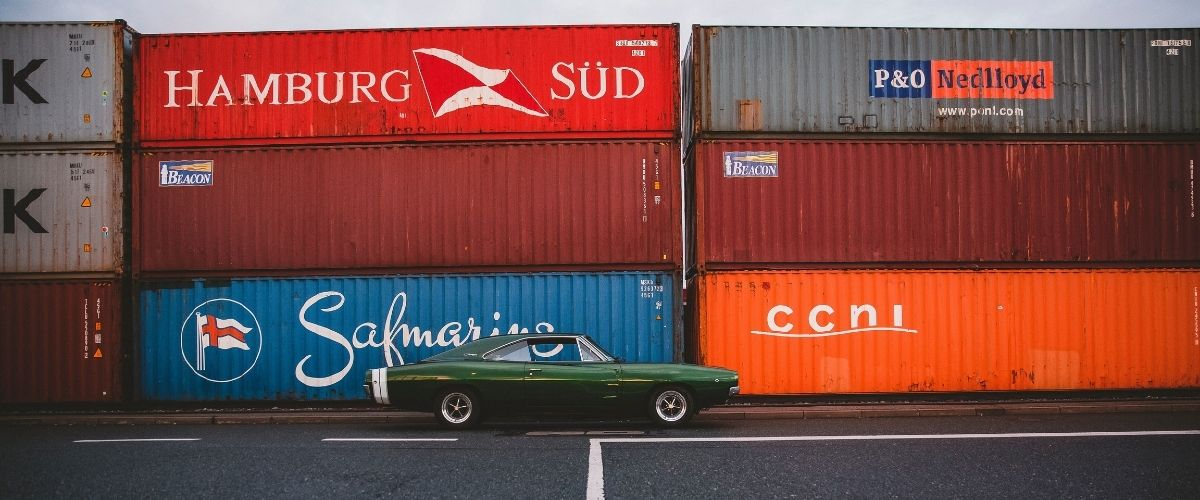 A nice car in front of shipping containers