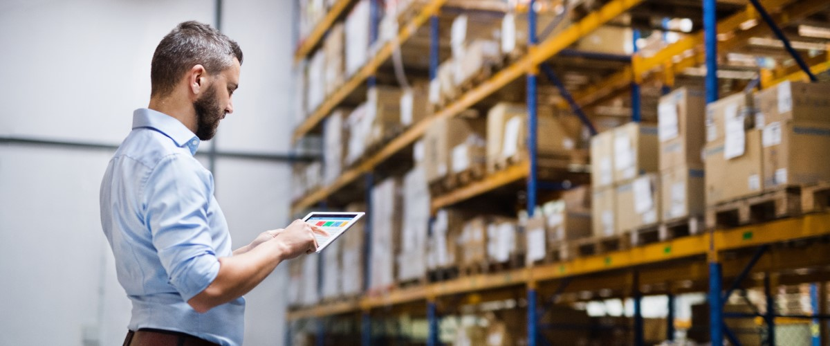 Man reviewing electronics inventory in a warehouse